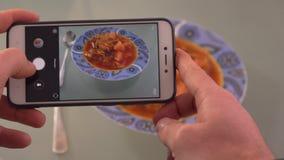 Ta ett foto av mat i en restaurang med mobiltelefonen tar ett foto av thai soppa för den tom sötpotatisen i en restaurang med mob stock video
