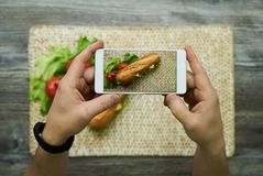 Ta ett foto på mobiltelefonen av den långa smörgåsen royaltyfri foto