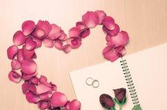 Ta ett rosa färgroskronblad in i hjärtaform arkivfoto