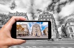 Ta färger ut ur svartvitt Kvinnlig hand med smartphon Royaltyfri Bild