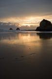 Ta foto av den härliga solnedgången på den sandiga stranden med klippor som reflekterar i vatten arkivbild