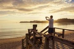 Ta foto av en härlig solnedgång med en smartphone royaltyfri fotografi