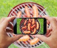 Ta fotoet av att grilla korvar vid smartphonen arkivbild
