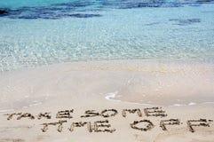 TA NÅGON LEDIGHET som är skriftlig på sand på en härlig strand, blåttvågor i bakgrund Royaltyfria Bilder