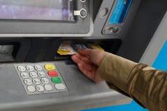 Ta pengar från en ATM Royaltyfri Bild