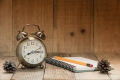 Ta tid på larmet, blyertspennan, anmärkningsbok, på trägolv Royaltyfri Fotografi