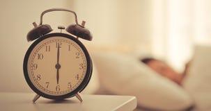 Ta tid på räkna till sex nolla klockan med kvinnan som fortfarande in sover Royaltyfri Foto