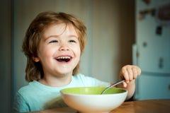 ?ta ungen Pys som har frukosten i k?ket Le lyckligt f?rtjusande behandla som ett barn ?ta frukt mosar i k?ket royaltyfria bilder