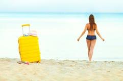 Żółta walizka na plaży i dziewczynie chodzi w morze w th Zdjęcia Royalty Free