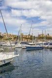 TA`XBIEX, MALTA - MARCH 9, 2018: Msida Yacht Marina with sailboats and the architecture of Ta Xbiex in the distance, at Marsamxet. TA`XBIEX, MALTA - MARCH 9 Stock Images