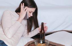 Taai gesprek aan vrouwen op de telefoon De jonge mooie vrouw drinkt bier royalty-vrije stock foto's