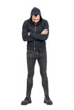 Taaie punker in zwart sweatshirt met een kap met gekruiste wapens die neer eruit zien Stock Foto's