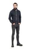 Taaie zekere modieuze punker in zwart sweatshirt die met een kap camera bekijken met dient zakken in Royalty-vrije Stock Afbeelding