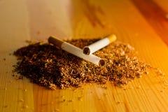 Tabaco y cigarrillos en el fondo de madera de la tabla Foto de archivo