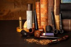 Tabak und alte Bücher Ablesen eines Kriminalromans Lizenzfreies Stockbild