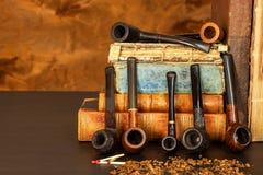 Tabak und alte Bücher Ablesen eines Kriminalromans Stockfotografie