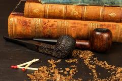 Tabak und alte Bücher Ablesen eines Kriminalromans Stockfoto