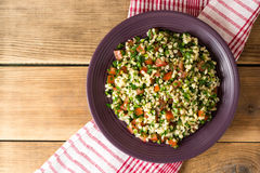 Tabbouleh salad with bulgur, tomatoes, parsley, green onion and mint in plate on wooden table. Stock Image