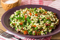 Tabbouleh salad with bulgur, tomatoes, parsley, green onion and mint in plate on wooden table. Stock Images