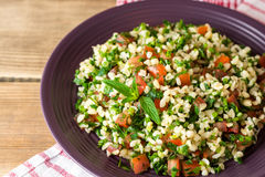 Tabbouleh salad with bulgur, tomatoes, parsley, green onion and mint in plate on wooden table. Royalty Free Stock Photo