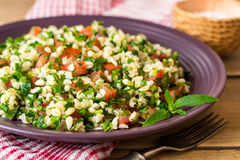 Tabbouleh salad with bulgur, tomatoes, parsley, green onion and mint in plate on wooden table. Royalty Free Stock Photography