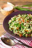 Tabbouleh salad with bulgur, tomatoes, parsley, green onion and mint in plate on wooden table. Stock Photo