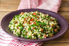 Tabbouleh salad with bulgur, tomatoes, parsley, green onion and mint in plate on wooden table. Stock Photography