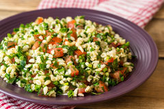 Tabbouleh salad with bulgur, tomatoes, parsley, green onion and mint in plate on wooden table. Royalty Free Stock Image