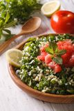 Tabbouleh salad closeup in a bowl and ingredients. Vertical Royalty Free Stock Photography