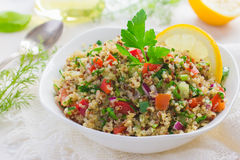 Tabbouleh salad with quinoa, parsley and vegetables. On white background Stock Photo