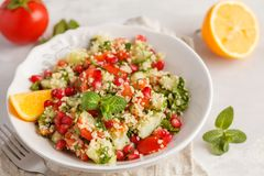 Tabbouleh salad with tomato, cucumber, couscous, mint and pomegranate. Vegan Healthy Food Concept. Traditional middle eastern or. Tabbouleh salad with tomato stock image