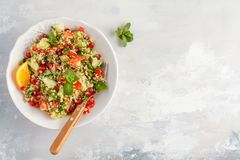 Tabbouleh salad with tomato, cucumber, couscous, mint and pomegranate. Top view, copy space, gray background. Vegan Healthy Food