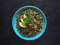 Tabbouleh sallad med couscous i en bunke på den svarta tabellen Levantine vegetarisk sallad med persilja, mintkaramell, bulgur, t Fotografering för Bildbyråer