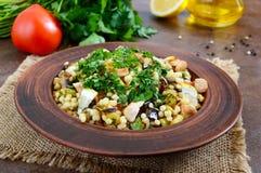 Tabbouleh - varm sallad av couscous, kött, stekte grönsaker och persilja arkivfoto