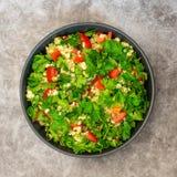 Tabboulehsalade met bulgur, peterselie, de lenteui en tomaat in kom op grijze achtergrond Hoogste mening stock afbeeldingen