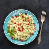 Tabboulehsalade met kouskous en granaatappelzaden op een blauwe plaat stock foto's