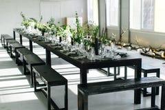 Tabela à moda, sótão Sala do projeto no estilo do sótão Tabela preta, cadeiras, pratos, velas Frascos com verdes imagem de stock royalty free