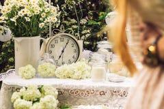 A tabela é decorada com branco, com pulsos de disparo velhos, velas, flores, margaridas em um vaso Foto de Stock
