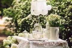 A tabela é decorada no branco com horas velhas, velas, flores, margaridas em um vaso, uma lâmpada de assoalho Foto de Stock
