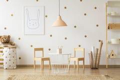 Tabela acima da lâmpada pastel entre cadeiras no interi da sala do ` s da criança do ouro imagens de stock royalty free