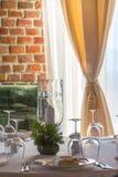 A tabela ajustou-se com velas em um restaurante luxuoso com parede de tijolo Imagem de Stock
