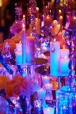 A tabela ajustou-se com velas para um evento, um partido ou um copo de água festivo, na luz roxa Fotografia de Stock
