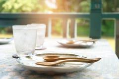 A tabela ajustou-se jantando com vidro da água e do woodware Foto de Stock