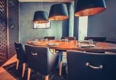 Tabela alaranjada, cadeiras azuis, lâmpadas Decoração do restaurante imagem de stock royalty free