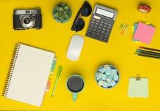 Tabela amarela da mesa de escritório com câmera, caderno, calculadora, xícara de café imagens de stock royalty free