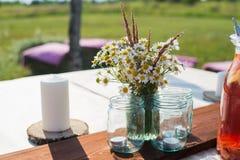 A tabela bonita ajustou-se com velas e flores para um evento, um partido ou um copo de água festivo Imagens de Stock Royalty Free