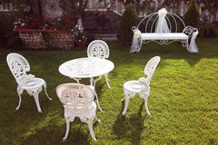 Tabela branca com as cadeiras no jardim Fotografia de Stock