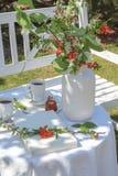 A tabela branca com café, caneles e flores serviu no jardim foto de stock
