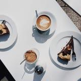 Tabela branca com o grandes latte do café e bolo de chocolate no sol imagens de stock