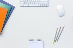 A tabela branca do escritório com cor do rato do teclado de computador escreve brochuras e outro fontes Fotografia de Stock Royalty Free